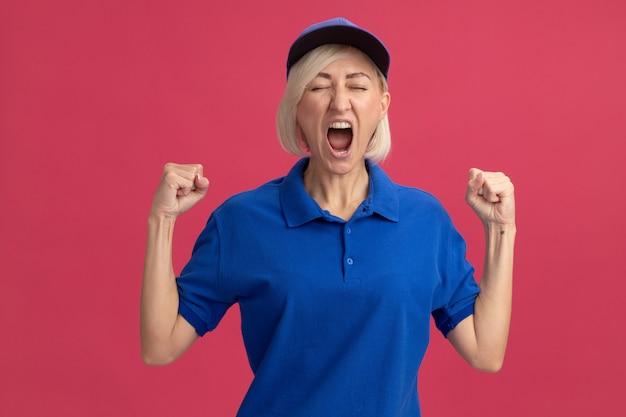 Joyeuse femme de livraison blonde d'âge moyen en uniforme bleu et casquette faisant un geste oui les yeux fermés