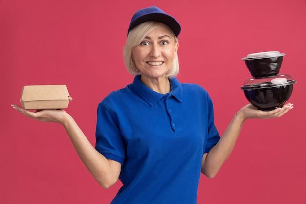 Joyeuse femme de livraison blonde d'âge moyen en uniforme bleu et casquette tenant un emballage alimentaire en papier et des récipients alimentaires