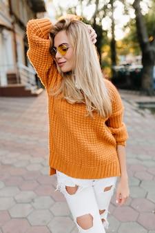 Joyeuse femme mince dans un joli cardigan tricoté profitant du temps libre en plein air et souriant