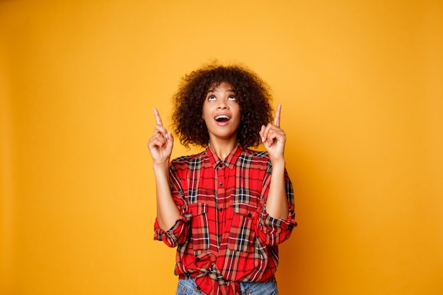 Joyeuse femme noire américaine en chemise rouge regardant vers le haut et pointant les doigts vers le haut sur l'espace de copie isolé sur fond orange.