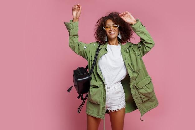 Joyeuse femme noire s'amusant sur un mur rose. t-shirt blanc, veste verte. look printanier élégant.