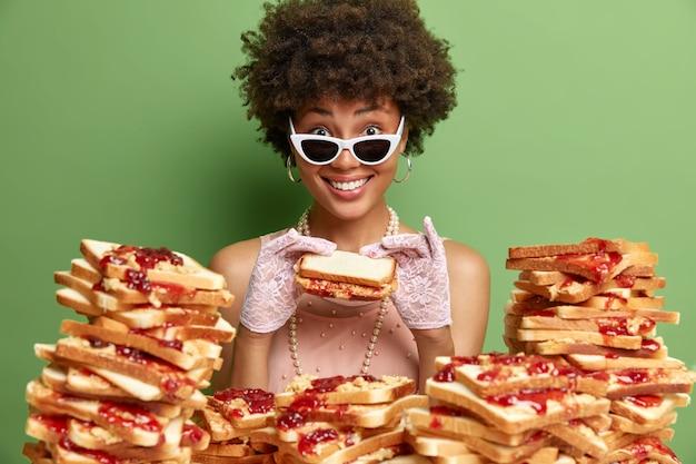 Joyeuse femme à la peau foncée avec des cheveux bouclés sourit mange agréablement un délicieux sandwich