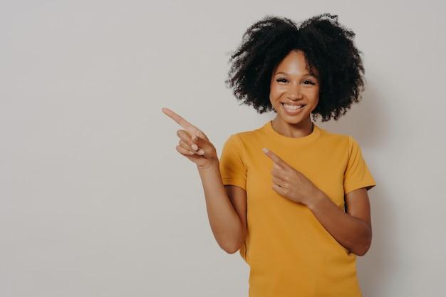 Joyeuse femme à la peau foncée vêtue d'un tshirt jaune pointant vers le coin supérieur gauche avec les index