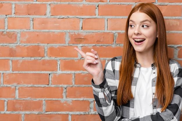Joyeuse femme pointant au mur de briques