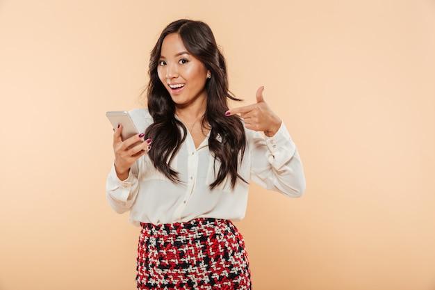 Joyeuse femme pointant le doigt sur son smartphone étant heureux d'utiliser un appareil électronique moderne sur fond beige