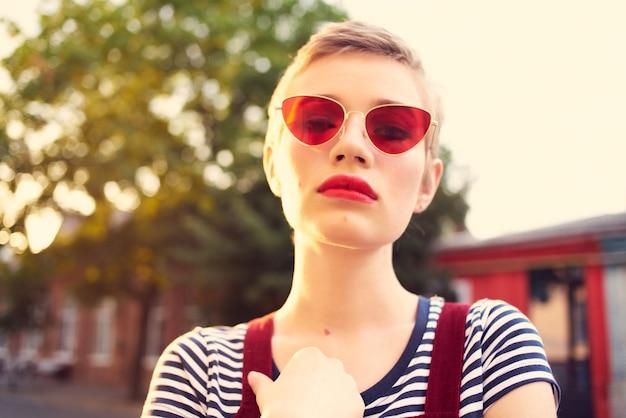 Joyeuse femme portant des lunettes de soleil à l'extérieur posant le mode de vie