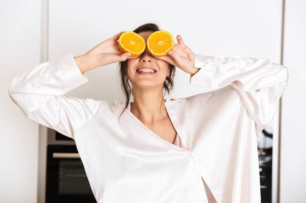 Joyeuse femme portant des vêtements en soie tenant deux morceaux d'orange, pendant le petit-déjeuner dans la cuisine à la maison