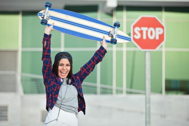 Joyeuse femme posant avec longboard