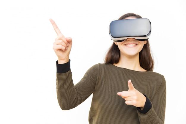 Joyeuse femme positive dans le casque vr pointant sur l'espace de copie
