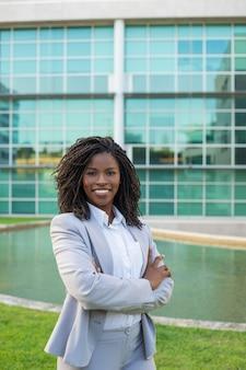 Joyeuse femme professionnelle souriante posant près du bureau