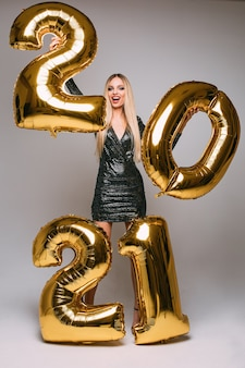 Joyeuse femme de race blanche aux longs cheveux blonds célèbre la nouvelle année 2021