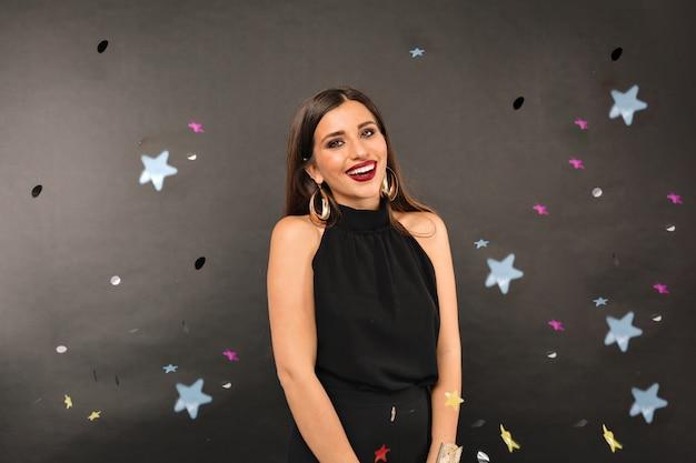 Joyeuse femme en robe noire célébration sous la douche de confettis