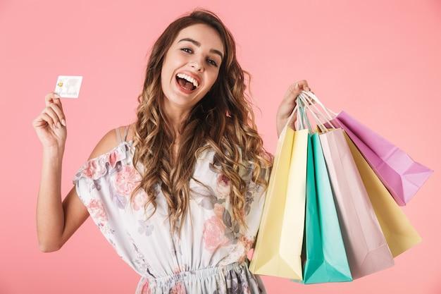 Joyeuse femme en robe tenant une carte de crédit et des sacs à provisions colorés, isolés sur rose