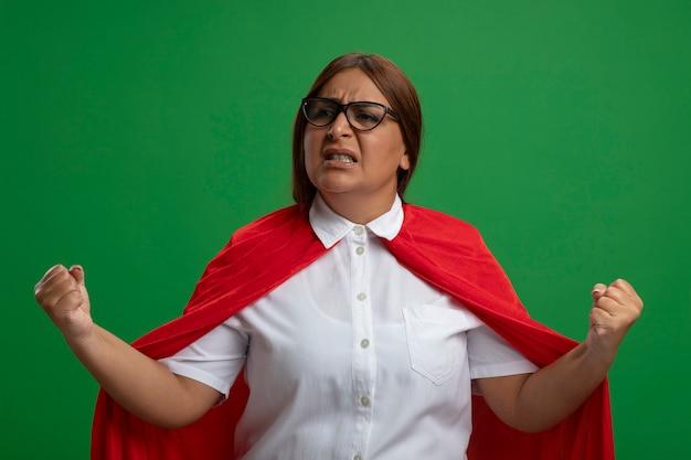 Joyeuse femme de super-héros d'âge moyen portant des lunettes montrant oui geste isolé sur vert