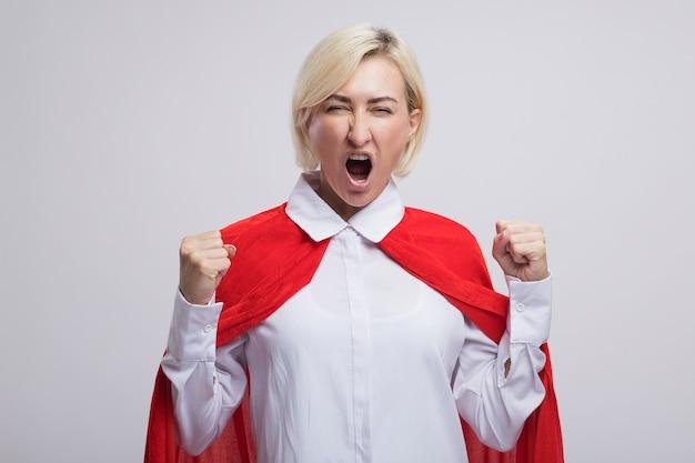 Joyeuse femme de super-héros blonde d'âge moyen en cape rouge faisant oui les yeux plissés geste