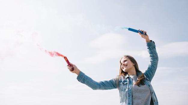 Joyeuse femme tenant des fusées éclairantes dans les mains tendues
