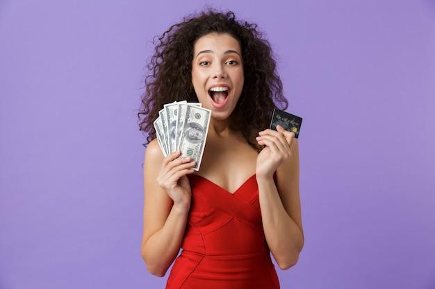 Joyeuse femme vêtue d'une robe rouge tenant un ventilateur d'argent et de carte de crédit, debout isolé sur mur violet