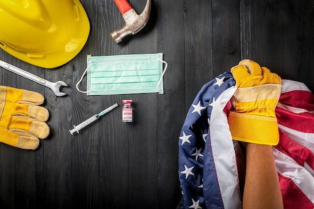 Joyeuse fête du travail pendant l'évasion des outils de travail du coronavirus, le gant tient le drapeau américain des états-unis