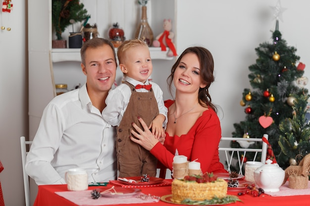 Joyeuse fête familiale de la nouvelle année, le père de la mère et le petit fils assis à la table