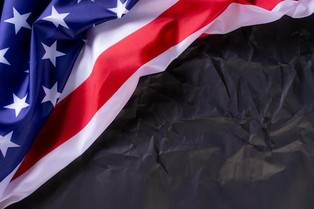 Joyeuse fête de l'indépendance, memorial day, fête des anciens combattants. drapeaux américains sur fond de papier noir.