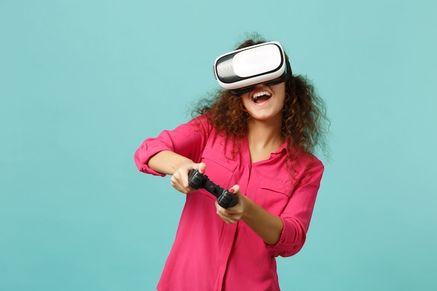 Joyeuse fille africaine dans des vêtements décontractés regardant dans un casque, jouant à un jeu vidéo avec une manette isolée sur fond de mur bleu turquoise. les gens émotions sincères, concept de style de vie. maquette de l'espace de copie.