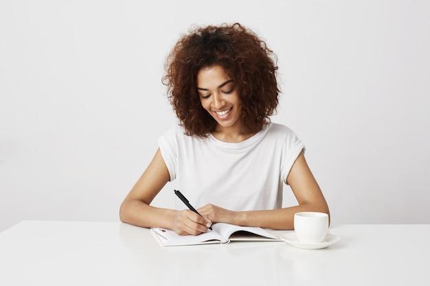 Joyeuse fille africaine souriant écrit dans le cahier au lieu de travail sur le mur blanc.