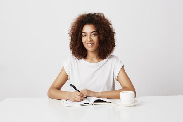 Joyeuse fille africaine souriant écrit dans le cahier sur le mur blanc.