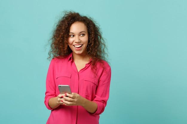 Joyeuse fille africaine en vêtements décontractés roses à l'aide d'un téléphone portable en tapant un message sms isolé sur fond de mur bleu turquoise en studio. les gens émotions sincères, concept de style de vie. maquette de l'espace de copie.