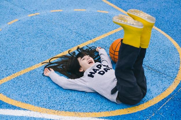 Joyeuse fille allongée près de la balle de basket-ball