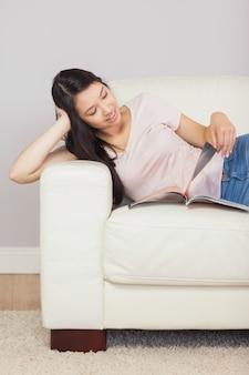 Joyeuse fille asiatique allongée sur le canapé en lisant un magazine