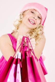 Joyeuse fille d'assistance du père noël avec des sacs à provisions