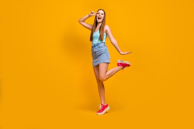 Joyeuse fille aux cheveux raides s'amusant montrant v-sign isolé sur fond jaune