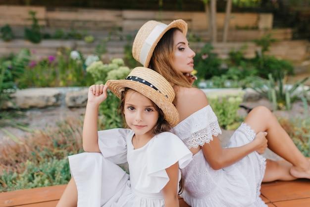 Joyeuse fille aux grands yeux assis à côté de la jeune mère pensive en costume blanc romantique. sérieuse femme aux cheveux longs posant dos à dos avec sa fille avec des fleurs.