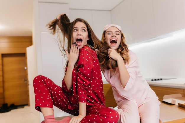 Joyeuse fille blonde en masque de sommeil jouant avec les cheveux d'un ami et riant. portrait intérieur de soeurs caucasiennes insouciantes s'amuser avant le petit déjeuner.