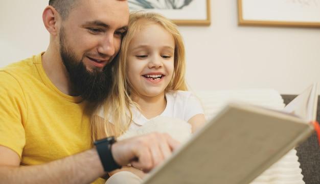 Joyeuse fille blonde et son père avec barbe lisant ensemble un livre