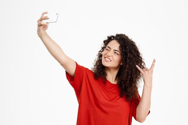 Joyeuse fille bouclée faire selfie