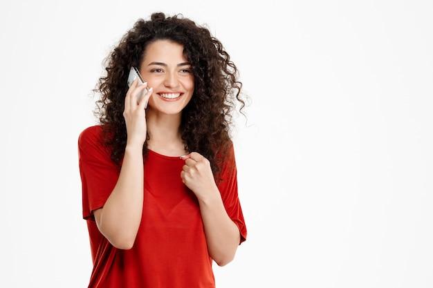 Joyeuse fille bouclée, parler sur son téléphone
