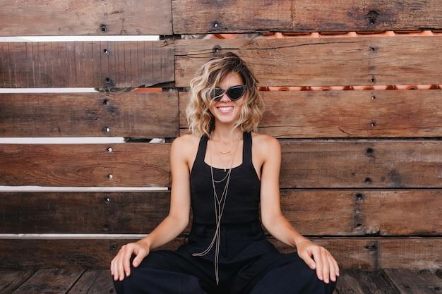 Joyeuse fille bronzée en tenue noire à la mode posant sur un mur en bois. portrait de charmante femme blonde dans des vêtements élégants, assis les jambes pliées.