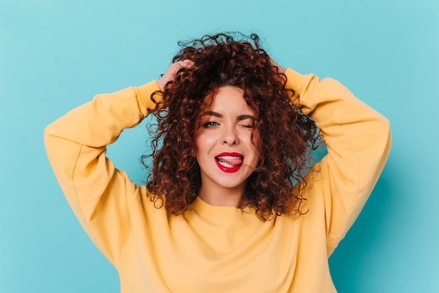 Joyeuse fille brune bouclée aux yeux bleus et rouge à lèvres clignote, touche les cheveux et montre la langue sur l'espace bleu.