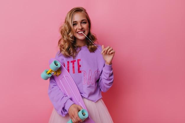 Joyeuse fille caucasienne avec bubble-gum s'amuser. incroyable femme blanche avec planche à roulettes debout sur rose.