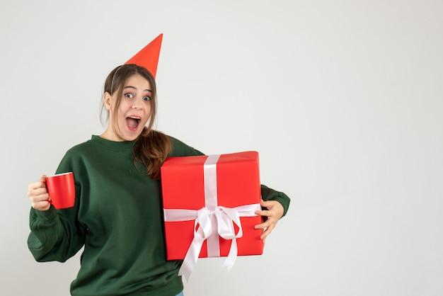 Joyeuse fille avec chapeau de fête tenant son cadeau de noël et une tasse de thé sur blanc