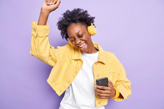 Joyeuse fille du millénaire aux cheveux bouclés danse insouciante aime playlsit préféré détient un téléphone mobile et des écouteurs modernes