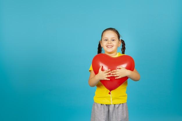 Joyeuse fille enthousiaste avec des nattes dans un t-shirt jaune embrasse un ballon rouge en forme de coeur