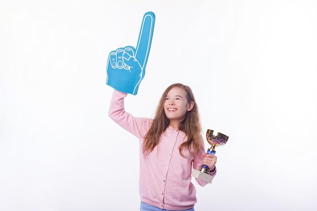 Joyeuse fille gagnante tient un trophée et un gant de fan foman.