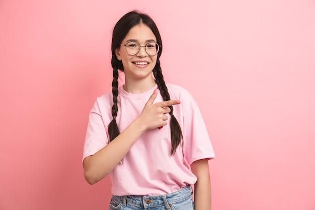 Joyeuse fille heureuse avec deux tresses portant des lunettes souriant et pointant les doigts de côté au fond isolé sur le mur rose