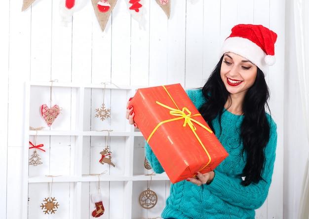 Joyeuse fille hispanique assis à l'intérieur décoré de noël vêtu d'un chapeau de père noël tenant une boîte cadeau rouge.