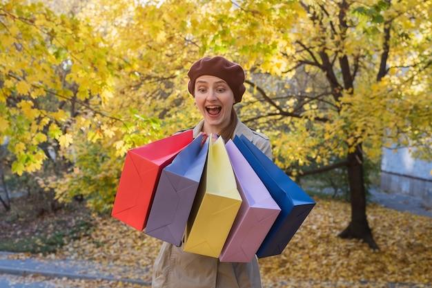 Joyeuse fille joyeuse avec des sacs colorés dans les mains. grande vente d'automne.