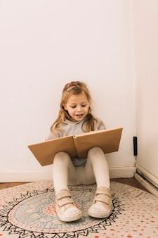 Joyeuse fille lisant près du mur