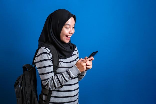 Joyeuse fille musulmane asiatique en train de naviguer sur internet ou de lire un message de discussion sur son téléphone