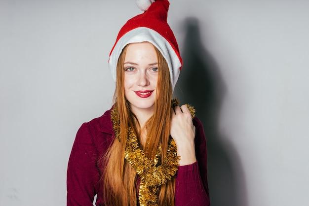 Joyeuse fille rousse dans un bonnet rouge comme le père noël et avec une guirlande d'or sur son cou en attendant noël